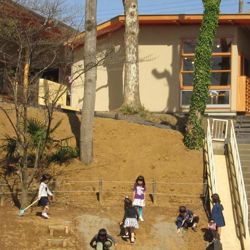 園庭の斜面で遊ぶ子供たち
